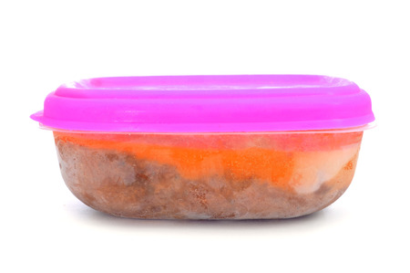 a plastic container with frozen food on a white background photo