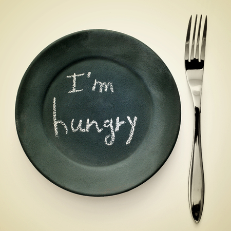 picture of a fork and a plate painted as a blackboard with the text I am hungry written in it on a beige background with a retro effect photo