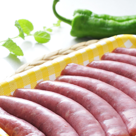 llonganissa: a pile of uncooked sausages in a plastic tray on a kitchen worktop