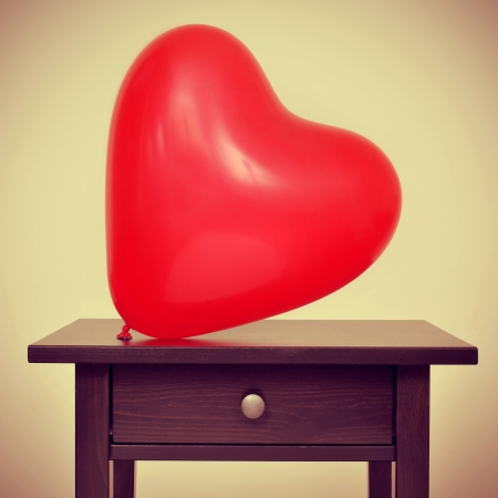 picture of a red heart-shaped balloon on a desk, with a retro effect photo