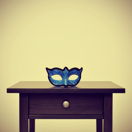 picture of a blue carnival mask on a desk, with a retro effect photo