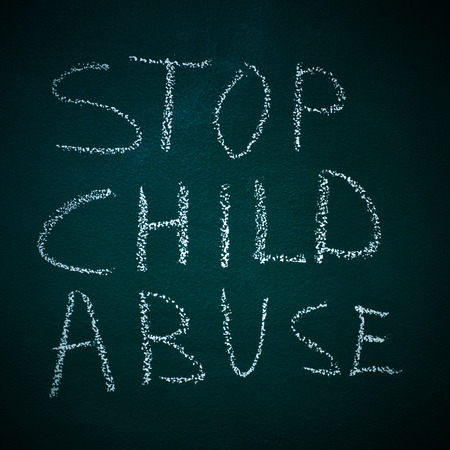 maltrato infantil: frase parada abuso infantil escrito en una pizarra Foto de archivo