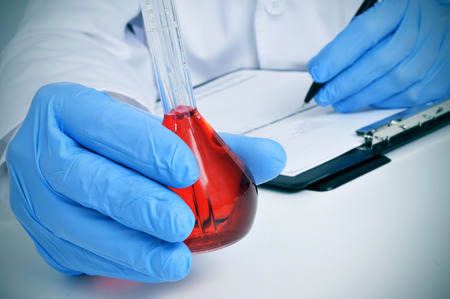 assays: man in white coat with a volumetric flask with a red liquid in a laboratory