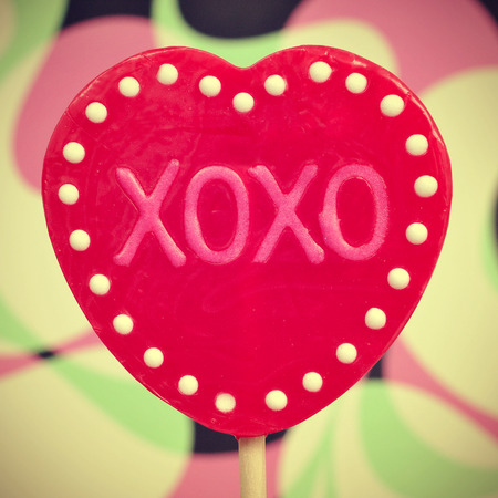 xoxo: picture of a heart-shaped lollipop with the text XOXO, hugs and kisses, written in it, with a retro effect Stock Photo