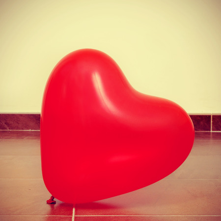picture of a red heart-shaped balloon on the floor, with a retro effect photo