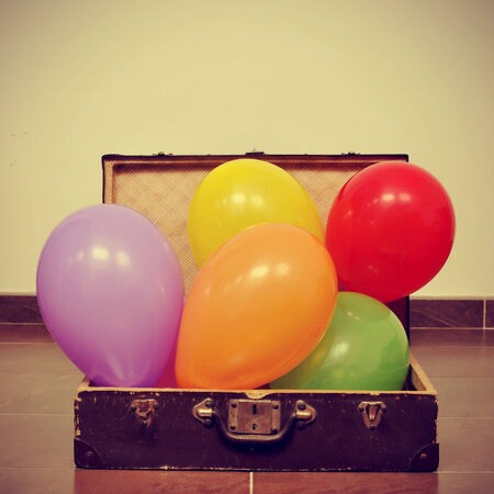 picture of a pile of balloons of different colors in an old suitcase, with a retro effect Stock Photo