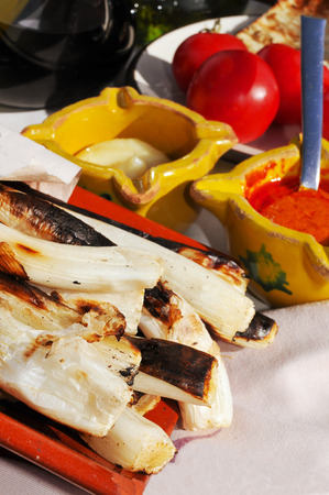 calsotada: closeup of a some barbecued calcots, sweet onions, and some mortars with romesco sauce and allioli, typical of Catalonia, Spain