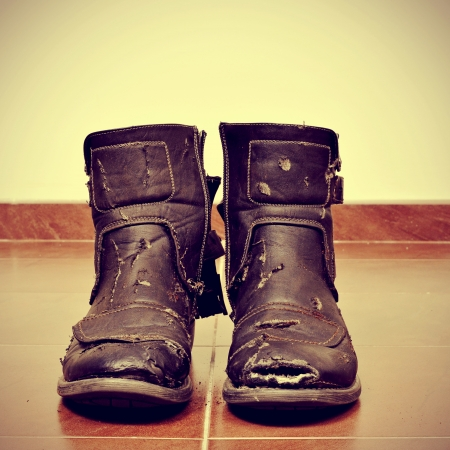 ratty: picture of a pair of worn and torn boots on the floor with a retro effect
