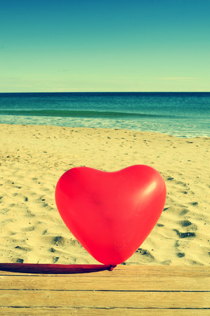 a red heart-shaped balloon on a beach, with a retro effect photo