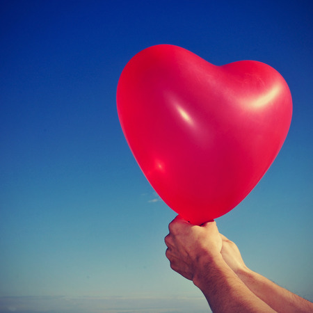 picture of someone holding a red heart-shaped balloon over the blue sky, with a retro effect photo