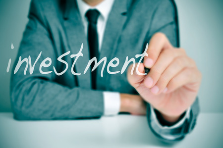 brokers: businessman sitting in a desk writing the word investment in the foreground