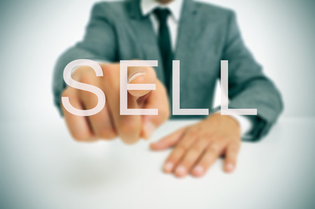sell shares: businessman sitting in a desk pointing the word sell written in the foreground