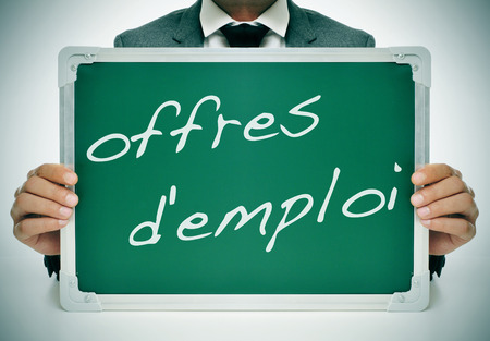 businessman sitting in a desk holding a chalkboard with the text offres demploi, jobs in french, written in it photo