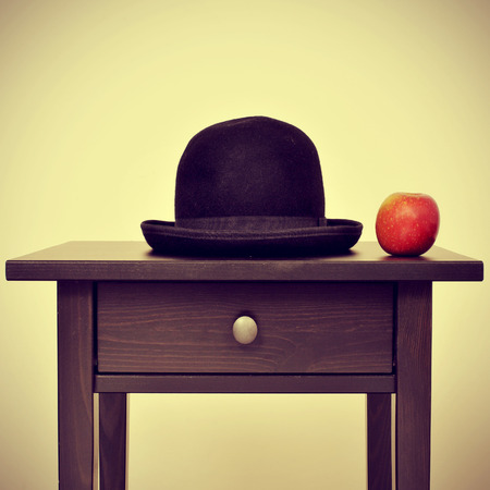 surrealism: picture of a bowler hat and an apple on a bureau, homage to Rene Magritte painting The Son of Man, with a retro effect Stock Photo