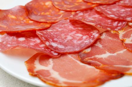 carnes: una bandeja con embutidos variados, español embutidos, como el chorizo, salchichón o lomo embuchado Foto de archivo