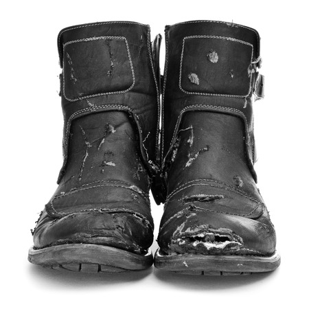 tatty: a pair of worn and torn boots on a white background