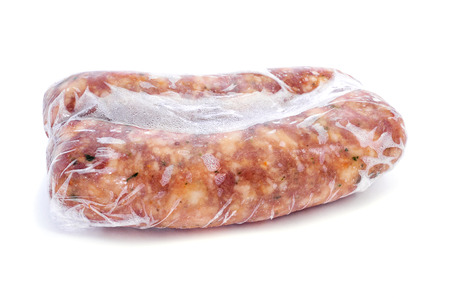 Frozen meat: some frozen spiced pork meat sausages wrapped in plastic wrap on a white background Stock Photo