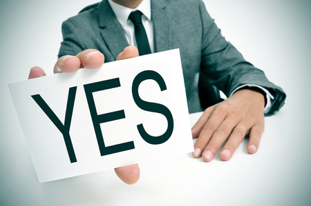 man wearing a suit sitting in a table showing a signboard with the word yes written in it photo