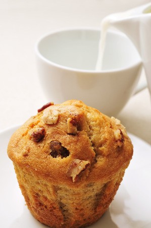 closeup of a muffin in a plate and a cup of milk on a set table photo