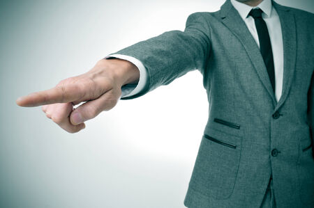 demotion: a man wearing a suit pointing with the finger the way out Stock Photo