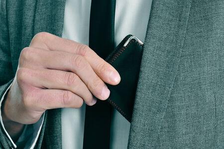 generoso: hombre que llevaba un traje de sacar su billetera de su chaqueta