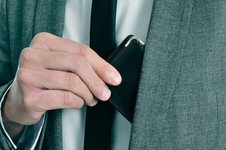 grudging: man wearing a suit taking out his wallet from his jacket