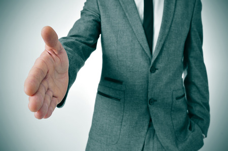 attend: man wearing a suit offering to shake hands Stock Photo