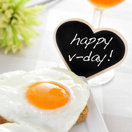 a heart-shaped fried egg on a toast and the text happy v-day written in a heart-shaped chalkboard photo