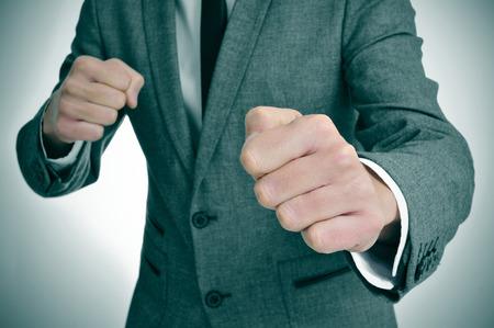 violence in the workplace: hombre que llevaba un traje con listo para pelear con los pu�os Foto de archivo