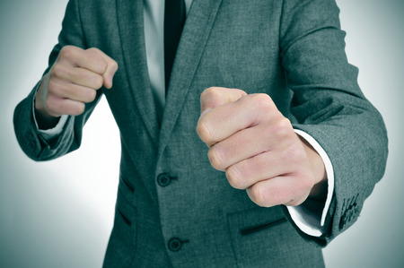 violence in the workplace: man wearing a suit with ready to fight with his fists Stock Photo