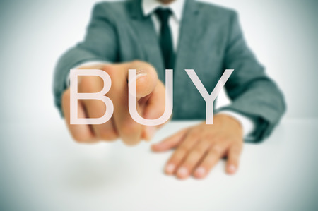 consumerist: businessman sitting in a desk pointing the word buy written in the foreground