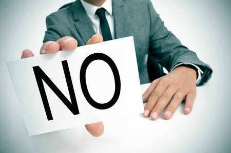 man wearing a suit sitting in a table showing a signboard with the word no written in it Stock Photo