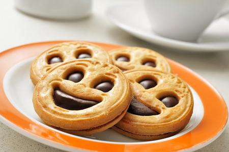 a plate with a pile of smiley biscuits and a cup of coffee in the background