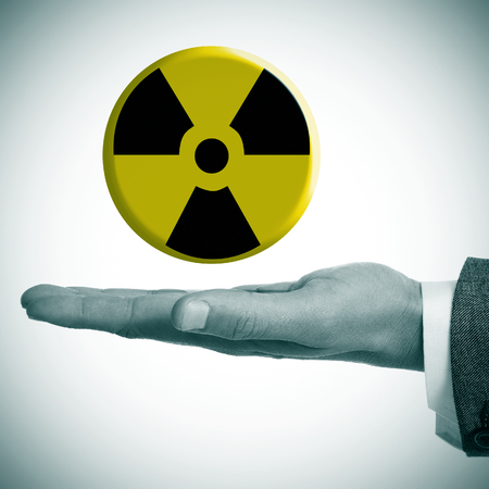 a man hand with a radiation warning symbol in his hand photo