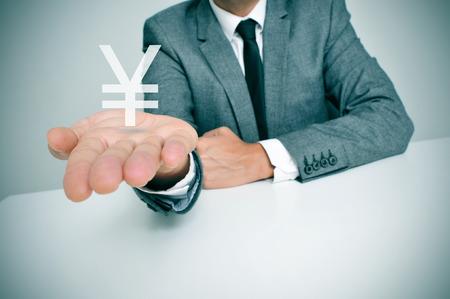 crisis economica: un hombre de negocios sentado en un escritorio que muestra un signo Yuan chino o el yen japonés en la mano Foto de archivo