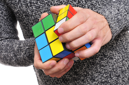 young man playing trying to solve a cube puzzle