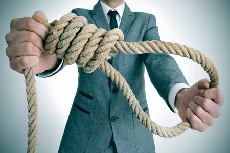 man wearing a suit holding a rope with a hangmans noose photo