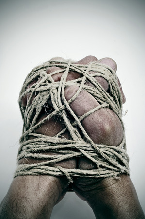 repression: man hands tied with string, as a symbol of oppression or repression, on a white background