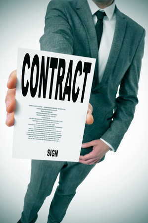 man wearing a suit showing a contract photo