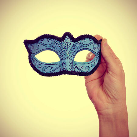 picture of a man hand holding a blue carnival mask on a beige background, with a retro effect photo