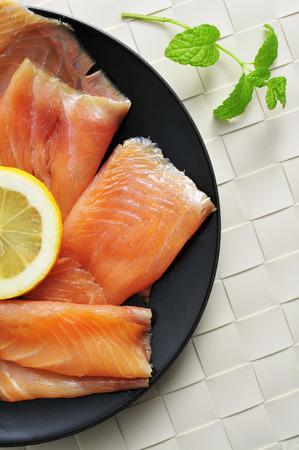 salmon ahumado: Primer plano de una placa con algunas rebanadas de salmón ahumado marinado con eneldo