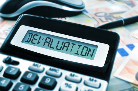 subprime mortgage crisis: word devaluation on the display of a calculator with euro bills in the background