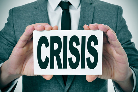 banking problems: a man wearing a signboard with the word crisis written in it