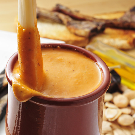 calsots: closeup of a barbecued calcot, sweet onion, dipped into a bowl with romesco sauce, typical of Catalonia, Spain Stock Photo