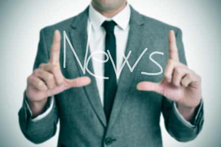 a man wearing a suit holding with his fingers the word news written in the foreground