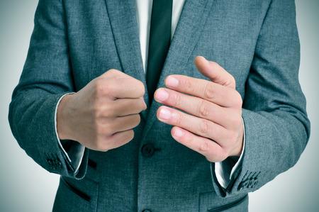 violence in the workplace: hombre que llevaba un traje de hombre de traje con un gesto de amenaza Foto de archivo