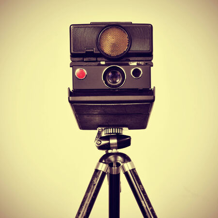 photojournalist: picture of an old instant camera in a tripod with a retro effect