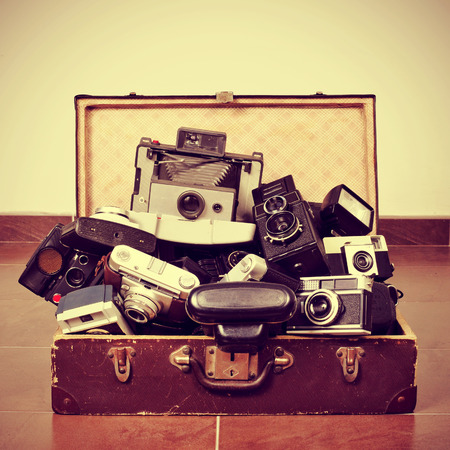 picture of a pile of old cameras in an old suitcase, with a retro effect photo