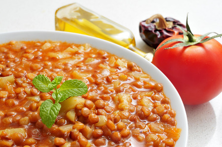 closeup of a bowl with lentil stew and olive oil and some vegetables in the background photo
