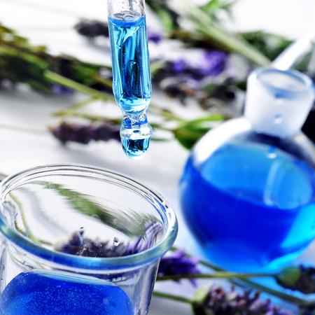 homeopatia: primer plano de una pipeta y un frasco con esencia de flores y un mont�n de flores de lavanda en el fondo